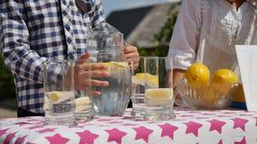 Duas crianças estão vendendo a limonada em um suporte de limonada caseiro em um dia ensolarado com um sinal do preço para um empr foto de stock