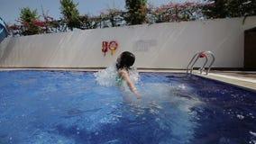 Duas crianças felizes, irmãs estão saltando na piscina no recurso Movimento lento vídeos de arquivo