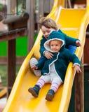 Duas crianças felizes na corrediça Foto de Stock Royalty Free