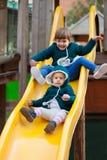Duas crianças felizes na corrediça no campo de jogos Fotos de Stock