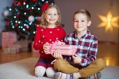 Duas crianças felizes na véspera de ano novo com presentes aproximam o ano novo T Fotografia de Stock Royalty Free