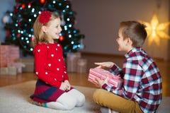 Duas crianças felizes na véspera de ano novo com presentes aproximam o ano novo T Imagem de Stock