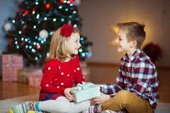 Duas crianças felizes na véspera de ano novo com presentes aproximam o ano novo T Imagens de Stock