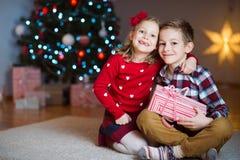 Duas crianças felizes na véspera de ano novo com presentes aproximam o ano novo T Fotografia de Stock