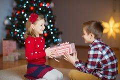 Duas crianças felizes na véspera de ano novo com presentes aproximam o ano novo T Foto de Stock Royalty Free