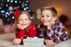 Duas crianças felizes na véspera de ano novo com presentes aproximam o ano novo T Imagens de Stock Royalty Free