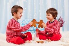 Duas crianças felizes que comem cookies no Natal e no leite bebendo fotografia de stock royalty free