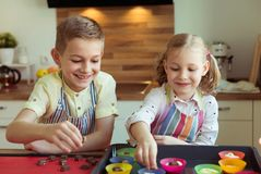 Duas crianças felizes que cozem cookies e queques do Natal no kitch Foto de Stock Royalty Free