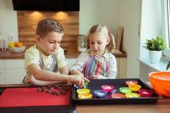 Duas crianças felizes que cozem cookies e queques do Natal no kitch Fotos de Stock
