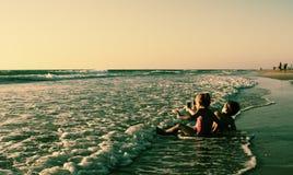 Duas crianças felizes que jogam na praia Fotos de Stock Royalty Free