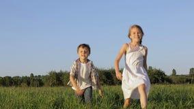 Duas crianças felizes que jogam no campo no tempo do dia vídeos de arquivo