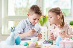 Duas crianças felizes que têm o divertimento durante a pintura eggs para easter dentro imagem de stock royalty free