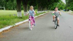 Duas crianças felizes - uma menina e um menino montam bicicletas na rua tiro do steadicam vídeos de arquivo
