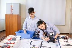Duas crianças, irmão com a irmã que enaging em seu robô deconstrução brincam imagens de stock