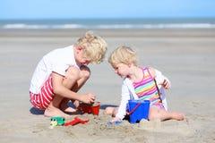 Duas crianças, irmão e irmã, jogando na praia fotografia de stock