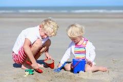 Duas crianças, irmão e irmã, jogando na praia fotografia de stock royalty free
