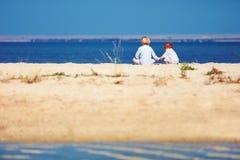 Duas crianças, irmãos que sentam-se no Sandy Beach na manhã na costa do lago Imagem de Stock