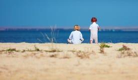 Duas crianças, irmãos que sentam-se no Sandy Beach na manhã perto do lago Foto de Stock Royalty Free