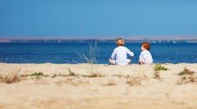 Duas crianças, irmãos que sentam-se no Sandy Beach na manhã perto do lago Imagem de Stock
