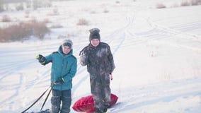 Duas crianças montam em um monte nevado em um trenó As crianças escalam à parte superior da montanha Caminhadas no ar fresco vídeos de arquivo