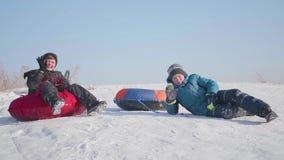 Duas crianças montam em um monte nevado em um trenó As crianças sentam-se sobre a montanha Esporte e atividades exteriores video estoque