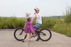 Duas crianças na bicicleta do dia de verão e o menino e a menina da flor Imagens de Stock Royalty Free