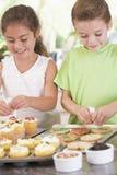 Duas crianças na cozinha que decoram bolinhos Imagem de Stock Royalty Free