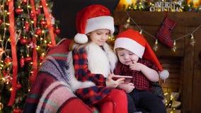 Duas crianças nas decorações do Natal que jogam o smartphone filme