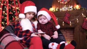 Duas crianças nas decorações do Natal que jogam o smartphone vídeos de arquivo