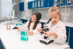 Duas crianças no laboratório revestem a aprendizagem da química no laboratório da escola Cientistas novos na fatura protetora dos foto de stock
