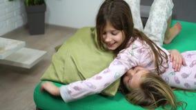 Duas crianças nos pijamas que lutam no sofá video estoque