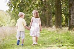 Duas crianças novas que andam nas mãos da terra arrendada do trajeto imagem de stock royalty free