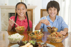 Duas crianças novas que comem o alimento chinês em jantar r Imagem de Stock