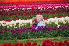 Duas crianças pequenas com caras infelizes são forçadas a levantar para as imagens que sentam-se em um campo de tulipas coloridos imagens de stock