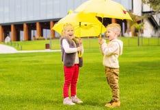 Duas crianças pequenas felizes que jogam com guarda-chuvas amarelos Foto de Stock Royalty Free