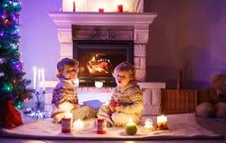 Duas crianças pequenas que sentam-se por uma chaminé em casa no Natal Fotografia de Stock Royalty Free