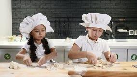 Duas crianças prées-escolar que trabalham de lado a lado cozinhando tortas e cookies Os cozinheiros chefe das crianças vestem cha filme