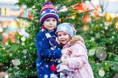Duas crianças que abraçam no mercado do Natal Fotografia de Stock