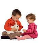 Duas crianças que alimentam um coelho Imagem de Stock