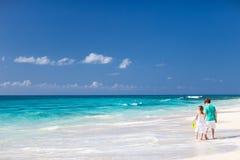 Duas crianças que andam ao longo de uma praia nas Caraíbas Foto de Stock