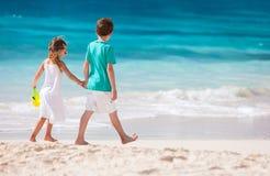 Duas crianças que andam ao longo de uma praia nas Caraíbas Imagem de Stock