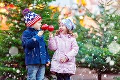 Duas crianças que comem a maçã do açúcar no mercado do Natal Fotos de Stock Royalty Free
