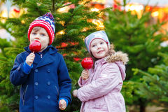 Duas crianças que comem a maçã do açúcar no mercado do Natal Foto de Stock Royalty Free