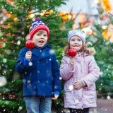 Duas crianças que comem a maçã do açúcar no mercado do Natal Imagem de Stock