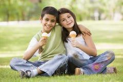 Duas crianças que comem o gelado no parque foto de stock