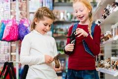 Duas crianças que compram brinquedos na loja de brinquedos Fotografia de Stock Royalty Free