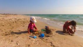 Duas crianças que constroem o castelo da areia na praia video estoque