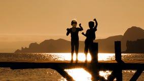 Duas crianças que dançam na ponte no por do sol