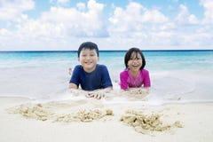Duas crianças que encontram-se na costa imagem de stock royalty free