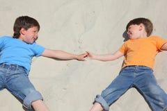 Duas crianças que encontram-se próximo na areia Fotos de Stock Royalty Free
